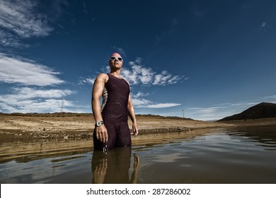 Close up wide angle view of a female triathlete standing waist deep in the water before she is about to train for a triathlon.