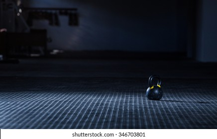 Close up wide angle view of a kettle bell weight on the floor of a gym with moody light.