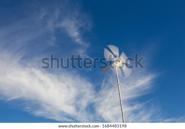 Cerrar la vista panorámica de una turbina eólica giratoria cargando baterías en una instalación de electricidad fuera de la red en una granja en el Karoo en el Cabo Occidental de Sudáfrica