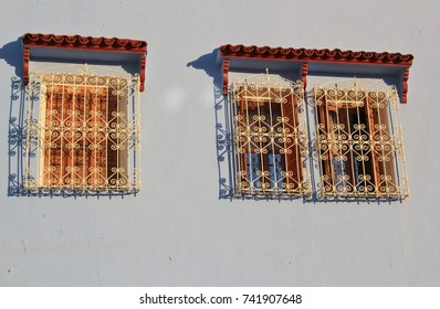 A close up windows decorated with golden metal lattice on blue wall. Chefchaouen, Morocco, North Africa.