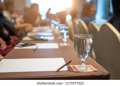 Close up  Wineglass of Water on Long Table with Blurred of People Sitting for Seminar and Coaching