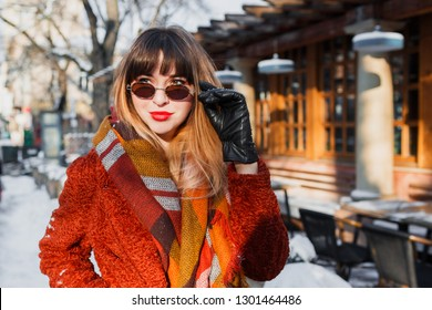 Close up winter portrait of elegant brunette woman in retro glasses posing outdoor in old European city. Standing near cafe. Wearing brown  coat, wool scarf and leather gloves.