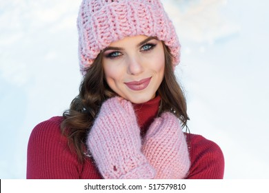 close up Winter portrait of a young smiling woman in a pink hat and gloves