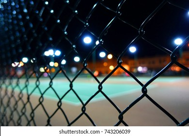 A close up of the wire mesh fencing around a tennis court with lights in the evening.