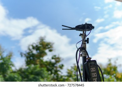 close up of wireless lan router or repeater for maximize radio signal more further with blue sky and cloud and tree.