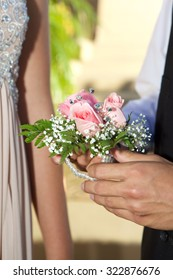 Close up of a wist corsage between a teenage boy and girl for a prom