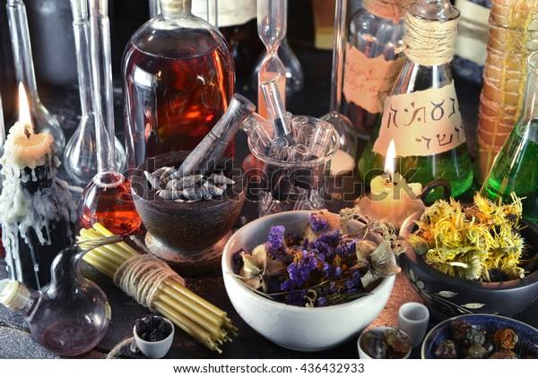 Nahaufnahme eines Hexenlabors mit Vintage-Kerzen, Glaswaren, Blumen und Kräutern. Halloween oder esoterisches Konzept. Alte Apotheke oder Alchimielabor. Schwarze Zauberobjekte und okkultistische Objekte, mittelalterliches alchemistisches Ritual
