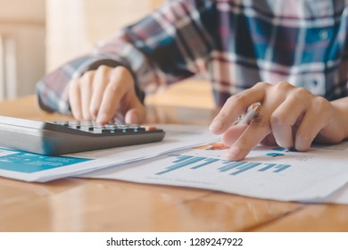 Close up of woman or accountant hand holding pen working on calculator to calculate business data, accountancy document and laptop computer at home, business concept - Image