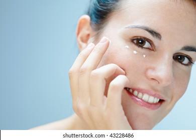 close up of woman applying eye cream
