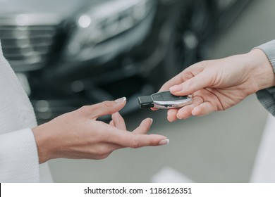 Close up woman arm taking key from seller of automobile. Car key handover concept