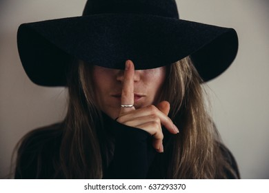 Close up of a woman in a black hat with face covered by hat, implying hushing with her finger in dark film vintage moody tones