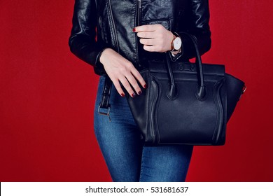 Close up woman black leather big bag in hand. Fashionable accessory watch
