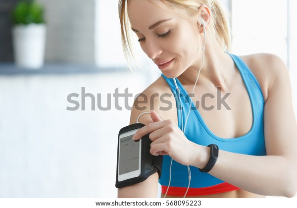 Close up of woman Body workout in fitness gym. Portrait of fit woman taking heart rate monitor and a mobile phone with headphones