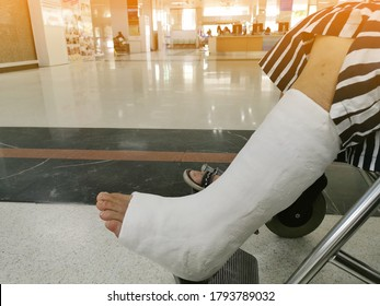 Close up a woman with a broken leg sit on a wheelchair at hospital. Leg bandaged in a plaster cast for fracture of the leg and ankle joint. Patient with broken leg from the accident. Selected focus.
