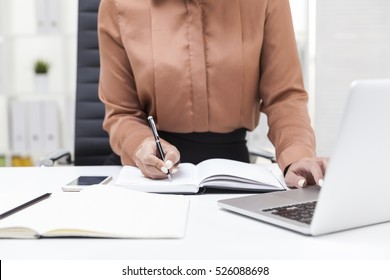 Close up of woman in brown blouse; taking notes with the second. Concept of secretary's job