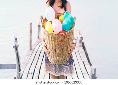 close up of woman carry  Balloons in basket full of love,at tropical beach coast,summer holiday concept background