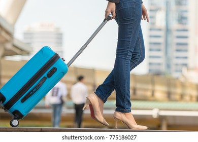 Close up of woman carrying suitcase at the airport terminal and hurry up for check in on holiday or business trip.