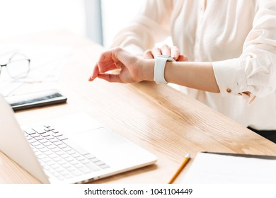 Close up of a woman checking time on her wrist watch while working at the office desk