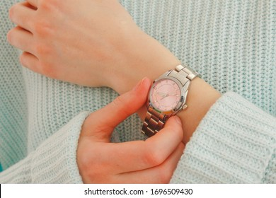 Close up  of a woman checking time on her luxury  pink watch. Selective focus of modern elegant  silver  wrist watch.Fashion accessory.