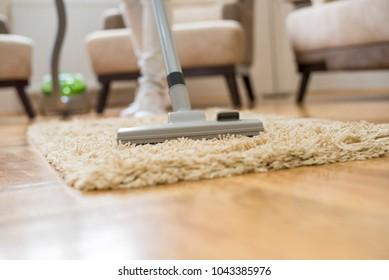 Close up of woman cleaning carpet with vacuum cleaner