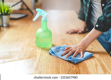 Close up woman cleaning kitchen using cleanser spray and cloth.