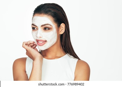 Close up of a woman with cosmetic facial mask applied over her face looking away.