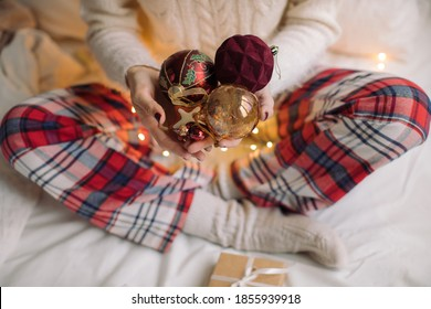 Close up of woman in cozy pajama sitting in bed and holding Christmas toys. Christmas, New Year, winter holidays background.
