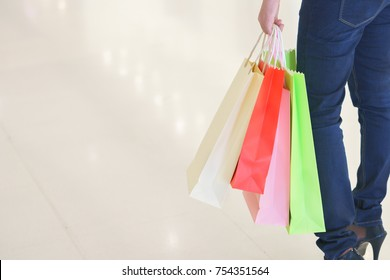 Close up of woman customer leg with colorful paper shopping bags