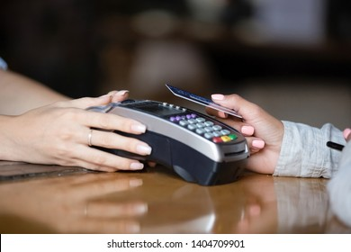 Close up woman, customer paying by plastic contactless credit card with  waitress holding card reader machine in hands on wooden bar counter, contactless payment concept