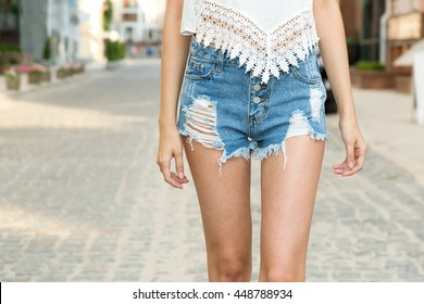 Close up of woman in denim shorts, front view. Young beautiful woman on the background of the city. Jeans clothes.