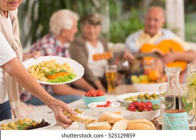 Close up of a woman dishing out a food, group of senior friends in the background