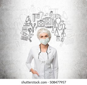 Close up of woman doctor in mask standing near concrete wall with medical sketches on it. Concept of healing