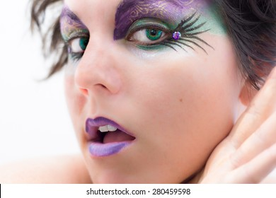 Close up of a woman with dramatic face painting around her eye. The paint is purple and green to match her green eyes.