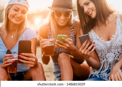 Close up of woman drinking beer and using mobile phone at music festival