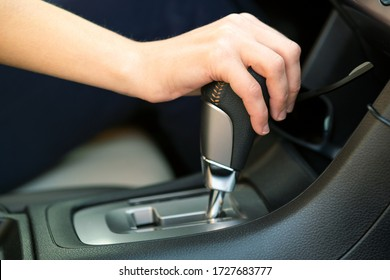 Close up of woman driver holding her hand on automatic gear shift stick driving as car.