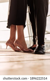 Close up a woman in elegant black dress and rose golden high heels staying together with her man in black pants and shoes. Elegant couple staying in front of sunlight on wooden floor near railings