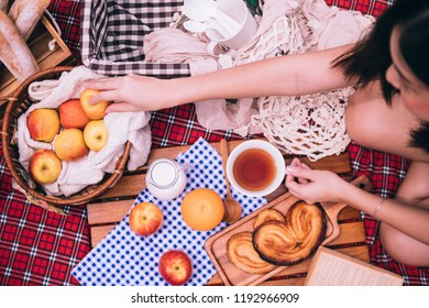 Close up of woman enjoying picnic in a park. Top view