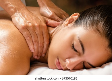 Close up of woman enjoying revitalizing shoulder and neck massage in spa.