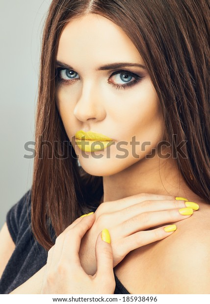 Close up woman face. Glamour make up portrait.Yellow lips and nails.