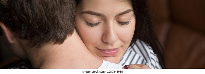 Close up woman face wife closed eyes embracing beloved husband, show love feels relieved. Support apology forgiveness empathy in relationship concept. Horizontal photo banner for website header design