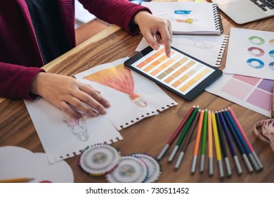 Close up of woman fashion designer at work drawing sketches for clothes in atelier with tailor tool and color charts, profession and job occupation, Fashion Designer Stylish Concept.