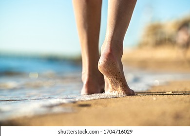Close up of woman feet walking barefoot on sand beach in sea water. Vacation, travel and freedom concept. People relaxing in summer.