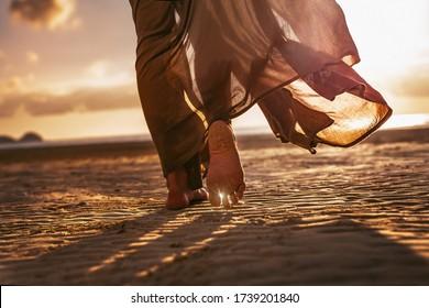 close up of woman feet walking onthe beach at sunset