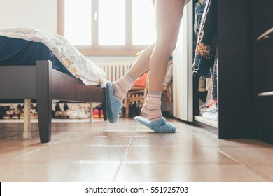 Close up woman feet wearing socks and slippers - morning, comfortable concept