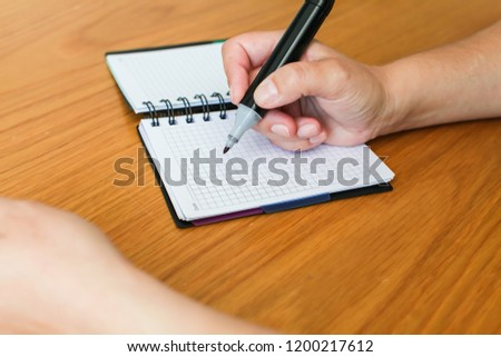 Close up Woman fills in to do list or goals in spiral notepad on wooden table, selective focus