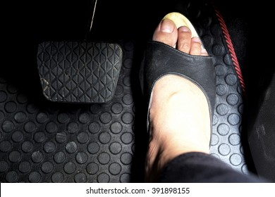 Close up of woman foot with black leather shoe on accelerator pedal in the car. Focus on black leather shoe.