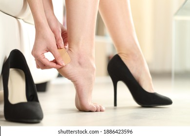 Close up of a woman foot in highheels putting a plaster on her heel at home