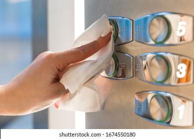 Close up of woman forefinger pressing the button in the elevator through a napkin, to protect yourself from contact with viruses, germs during a coronavirus pandemic, covid-19. Quarantine concept