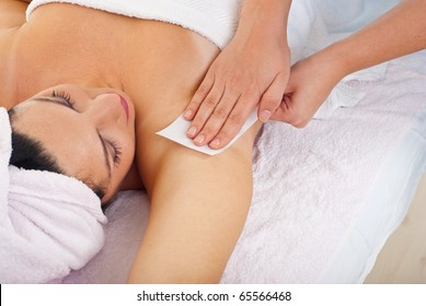 Close up of woman getting waxing armpit b y beautician in a beauty salon