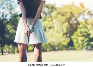 Close up of woman golf player hand at golf club, with empty copy space. Female golf player pitching at golf course with grass in the air.